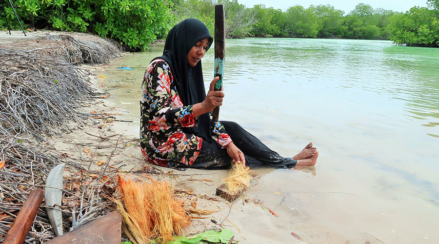 A woman is beating soaked coconut husk which was buried in Baarah mangrove swamp for a month with a wooden club to separate fibre to make rope.